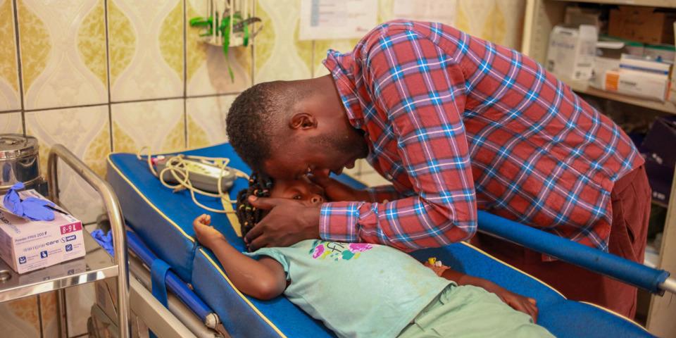 爸爸正在安慰受傷的女兒,也使她分心不要去注意腳上的玻璃和血。©Scott Hamilton