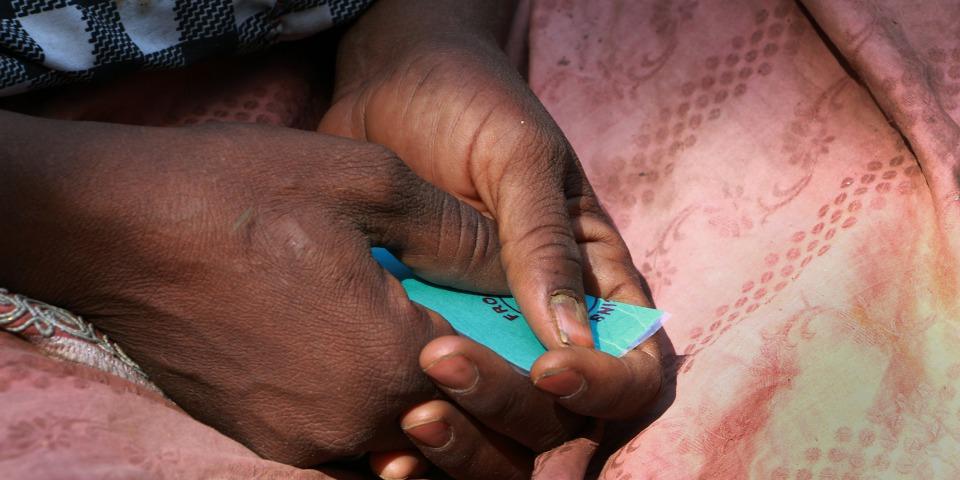 哈魯納手中拿著票券,以獲得無國界醫生分發的糧食。 © Malik Samuel/MSF