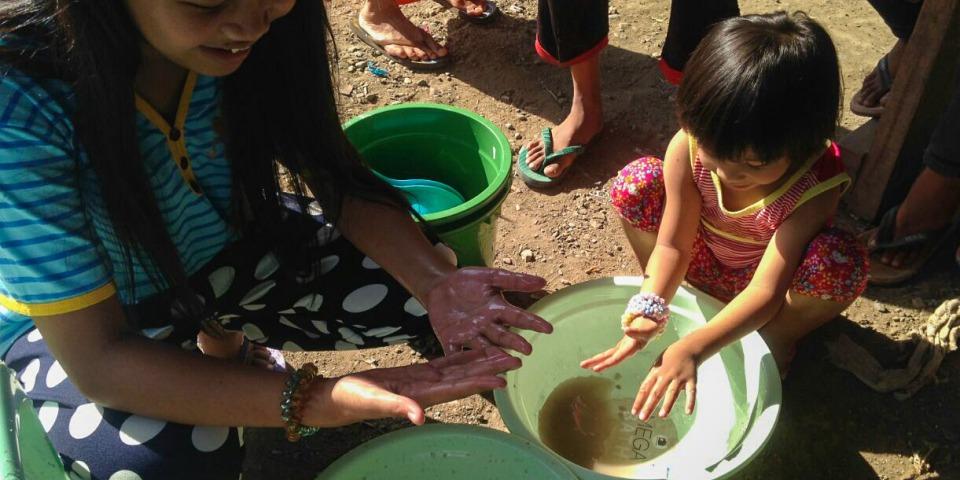 無國界醫生衛生推廣員為家長及孩子示範正確的洗手方法以防疾病傳播。© MSF