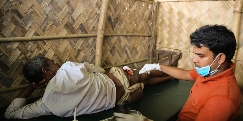 一名羅興亞難民逃難到孟加拉途中遭槍擊,一名無國界醫生人員正治理他的傷口。©Mohammad Ghannam/MSF