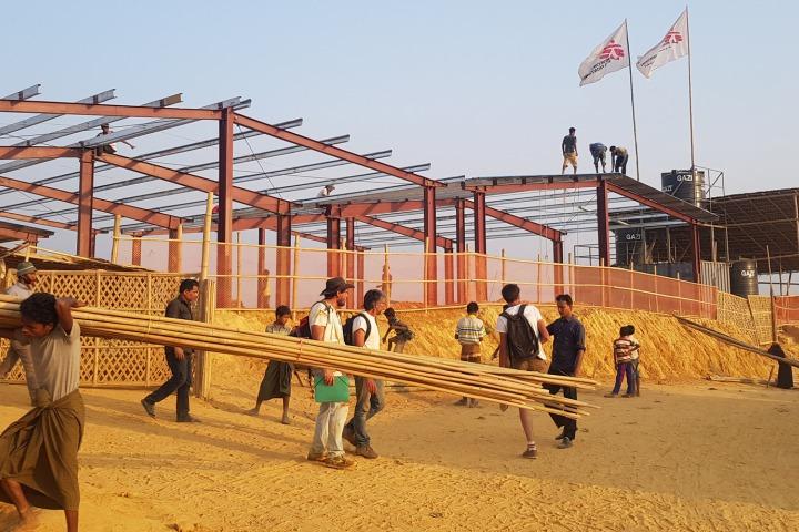 醫院建造過程:建築物鋼架將架上混凝土板,周圍圍上竹籬。©MSF