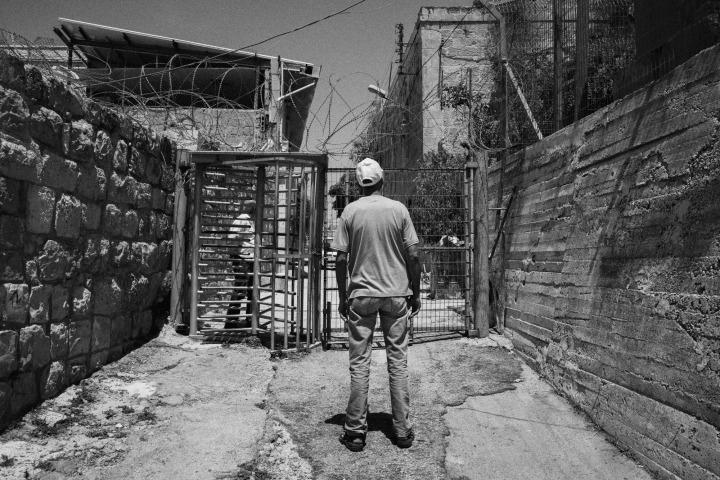 希伯倫市部分地區由以色列軍方控制。在以方設置的檢查站和圍欄分隔下,巴勒斯坦人的行動自由嚴重受限,阻礙了平民求職、上學或探訪親友。© Moises Saman/Magnum Photos