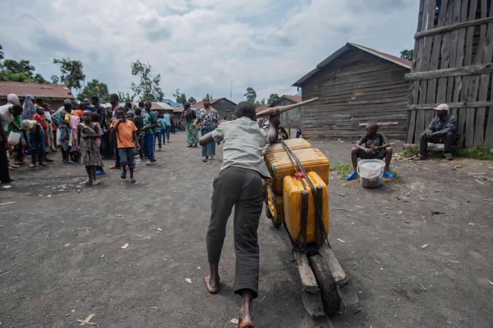 一名男子用當地的一種雙輪木車載送水桶。©MOSES SAWASAWA