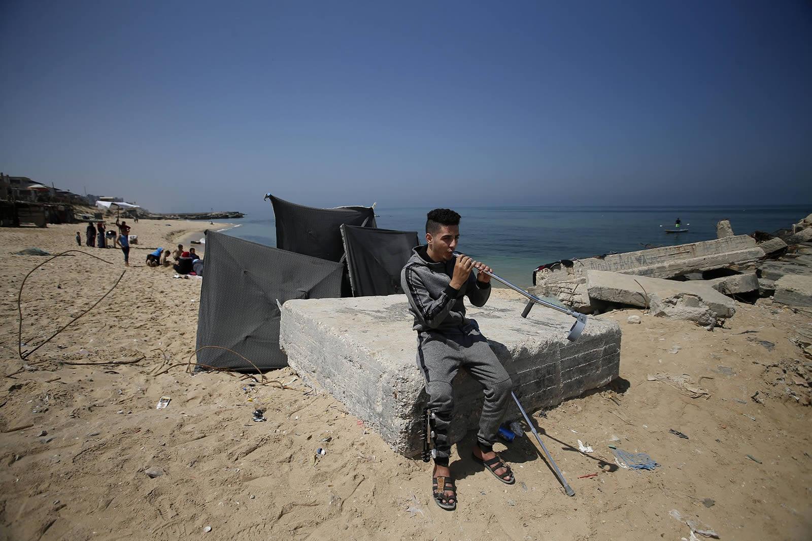 伊亞德在海邊吹著他用拐杖改造的笛子。©Mohammed ABED
