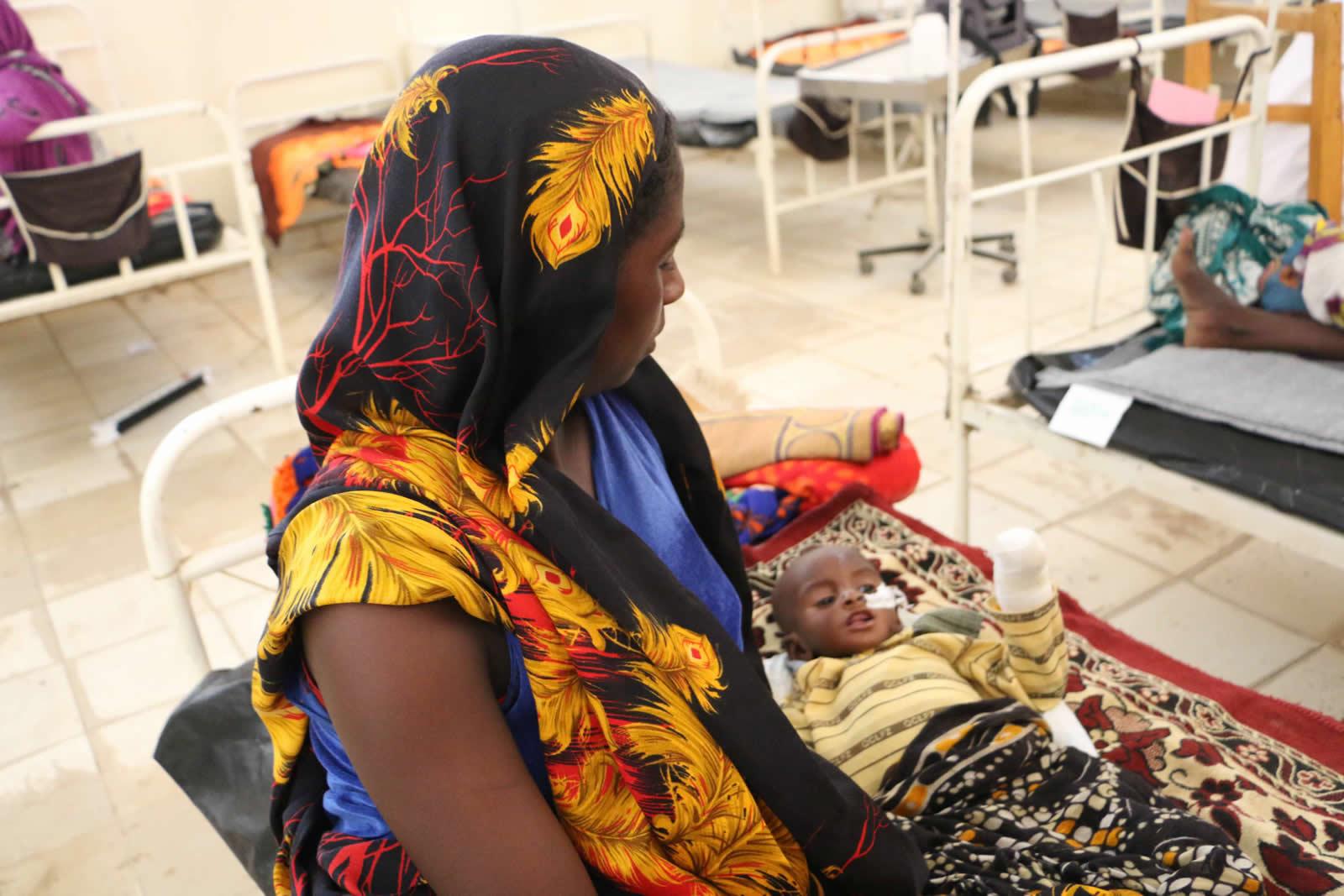 19歲的凡納(Fanna)抱著她的孩子坐在營養中心的床上。
