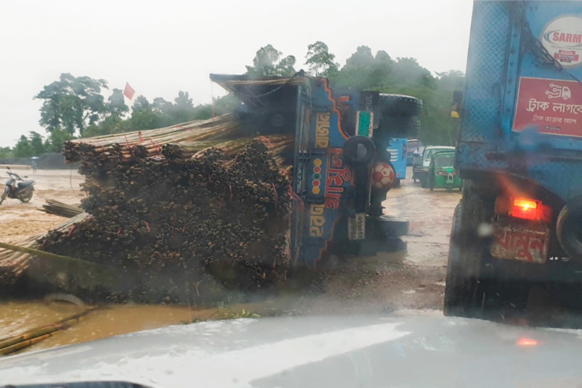 卡車載著沉甸甸的竹子在營區裡穿梭,用來搭建臨時棲身處和醫療設施。但因為道路泥濘不平,這輛卡車在我們的汽車前方側翻了。