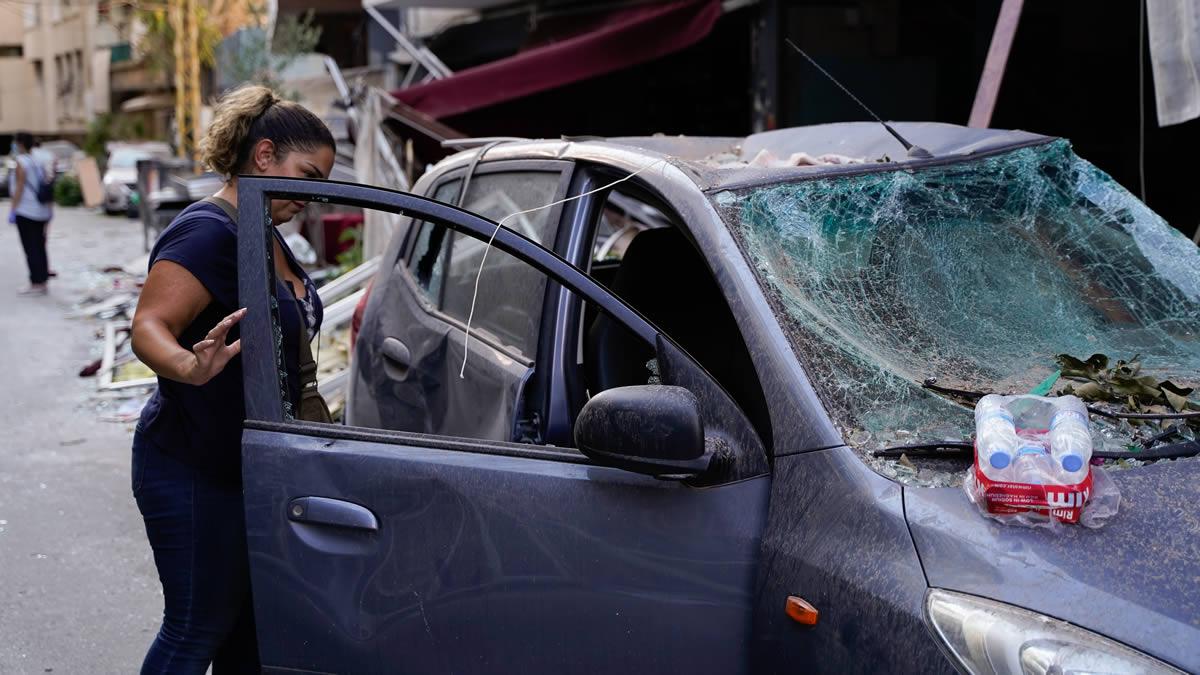 黎巴嫩貝魯特大爆炸,一位女士查看親戚受損的車子。