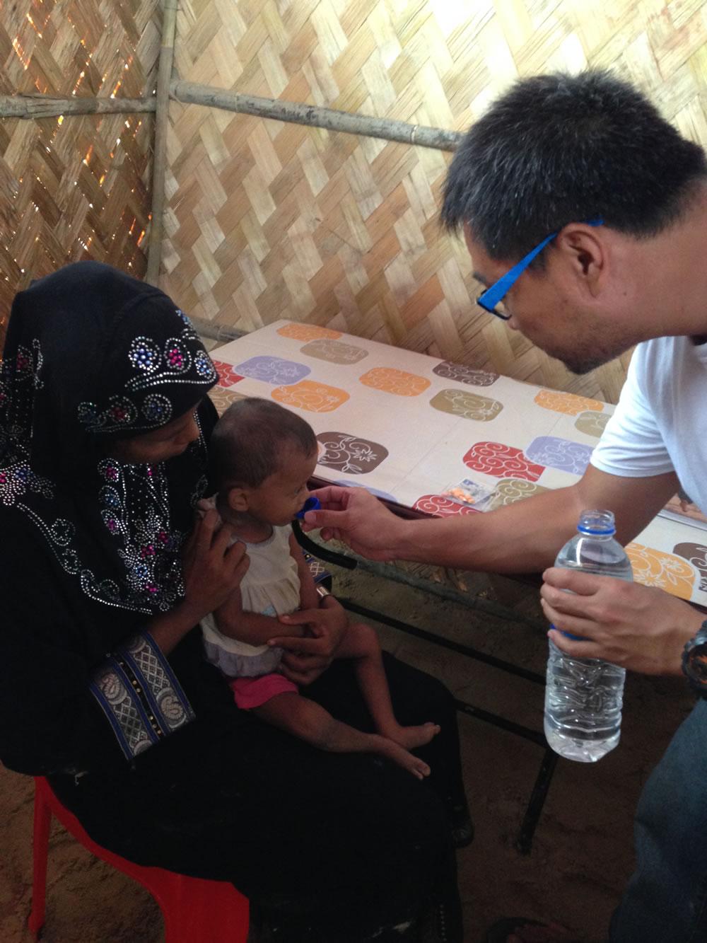 救援人員協助中度脫水病童飲用口服補充鹽液,並教導病童母親該如何餵他飲用。©Chiu Cheuk Pong