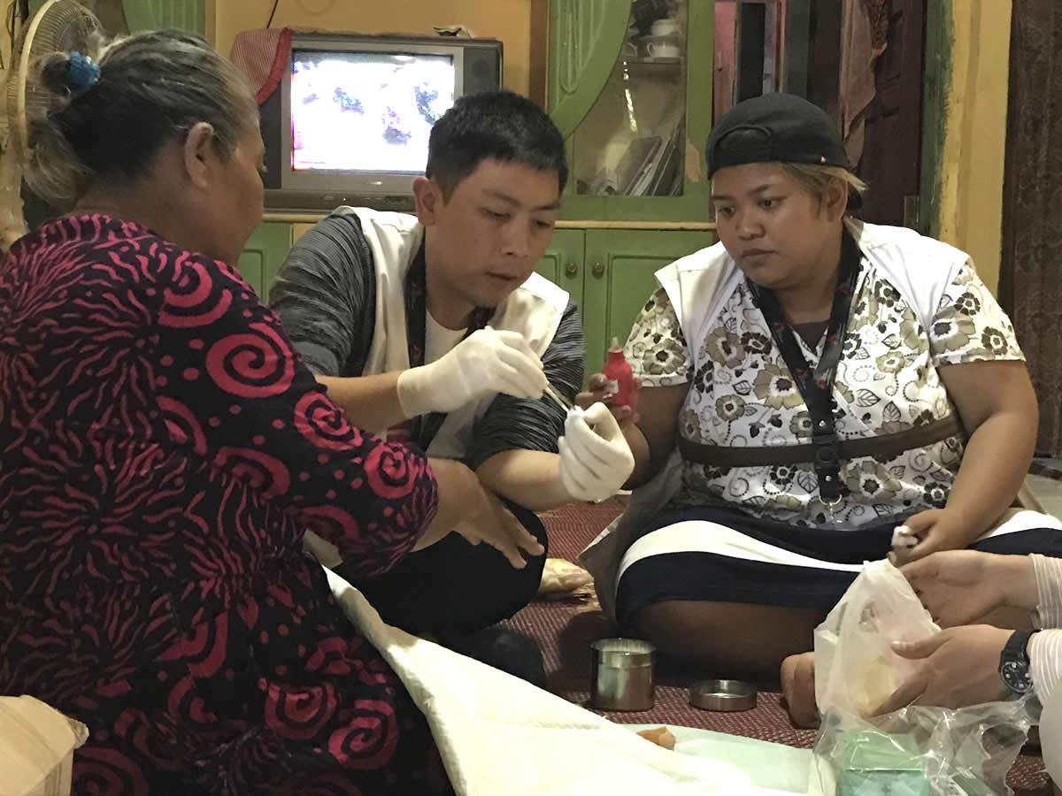 無國界醫生的醫師正在重新包紮艾利斯母親的傷口。她在海嘯中受傷,她的家也被摧毀。