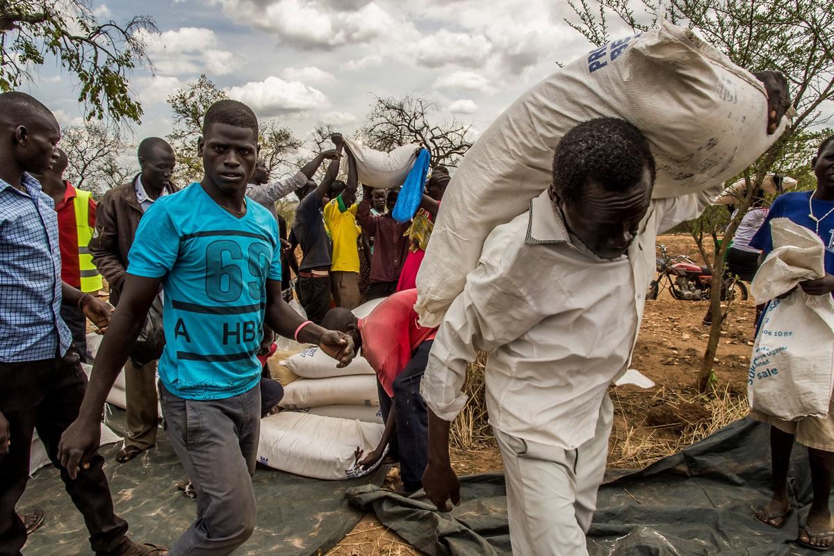 因資金短缺,聯合國世界糧食計劃署減少每月配給食物份量。與此同時,持續乾旱令烏干達北部的糧食價格居高不下。糧食缺乏保障是一個主要問題。圖為難民們領取配給糧食的情況。© Frederic NOY/COSMOS