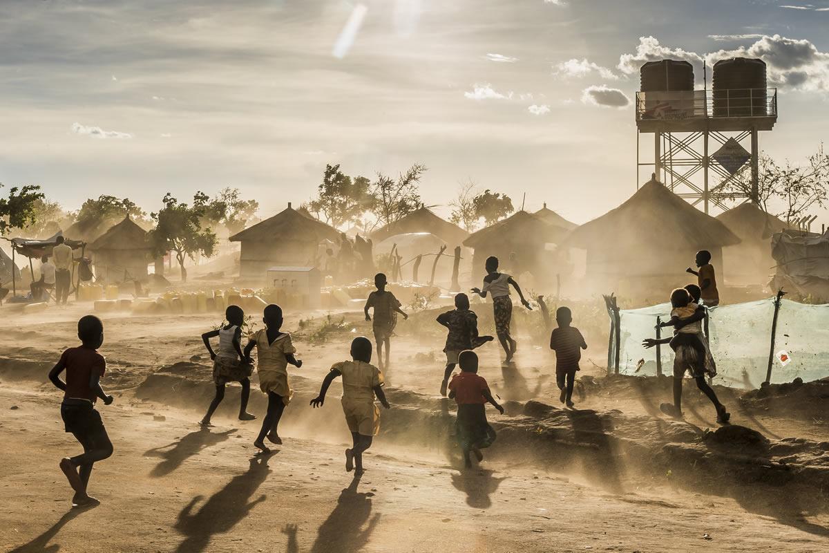 小孩在比迪比迪難民安置區內玩耍。他們眼前正是無國界醫生為難民提供的帳篷和水箱。© Frederic NOY/COSMOS